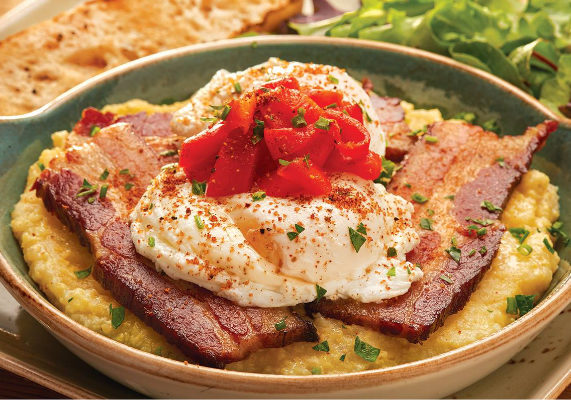 First Watch is adding a new breakfast entrée to its menu. The Pork Belly Bacon & Grits features Bob's Red Mill cheddar parmesan cheese grits topped with thick-cut braised pork-belly bacon, two poached cage-free eggs, pickled peppers and herbs served with lemon dressed organic mixed greens and ciabatta toast.