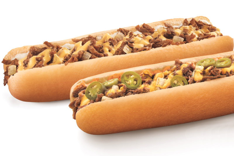 Sonic is serving new Footlong Philly sandwiches in classic and spicy varieties. The classic sandwich features grilled steak and onions topped with melted cheese sauce in a footlong bun, while the spicy variety adds sliced jalapeños and a zesty Baja sauce.