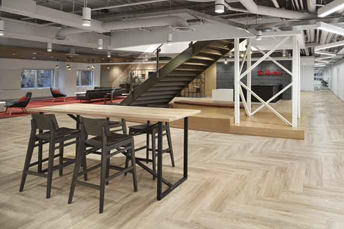 The reception area at Tim Hortons' new headquarters features wood flooring, exposed brick and natural lighting. Source: A Frame Inc.