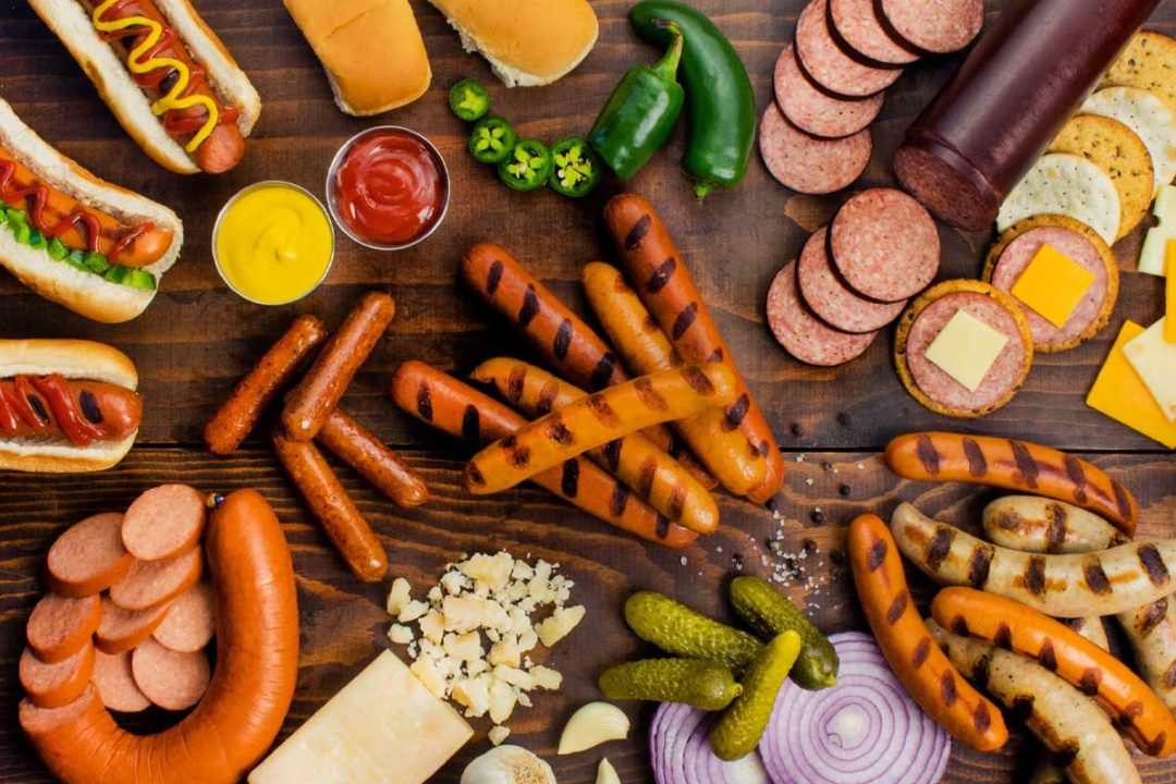 An assortment of sausages, hot dogs and condiments