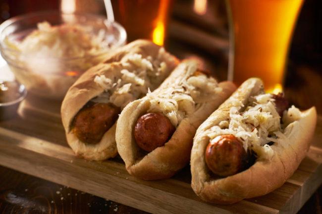 Three beer bratwursts in hot dog buns covered in sauerkraut