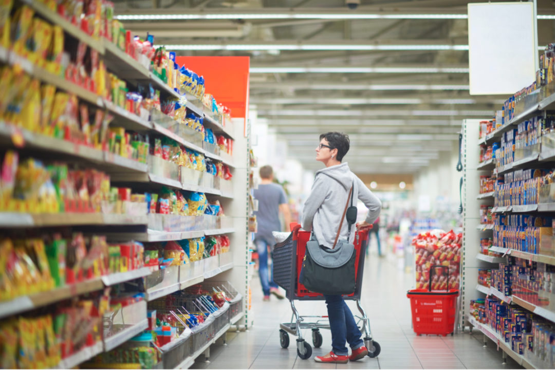 Woman scanning supermarket shelves