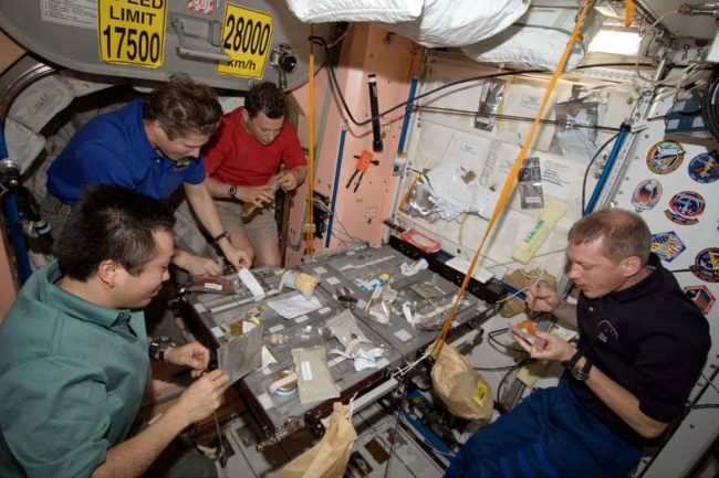Crew members share a meal in the Unity Module of the International Space Station.