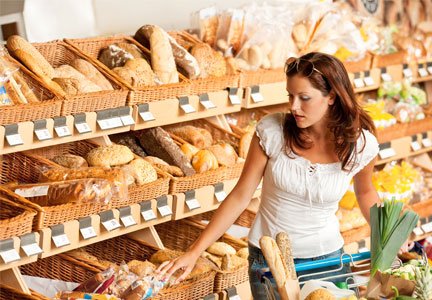 Woman choosing bread in bakery section of grocery store