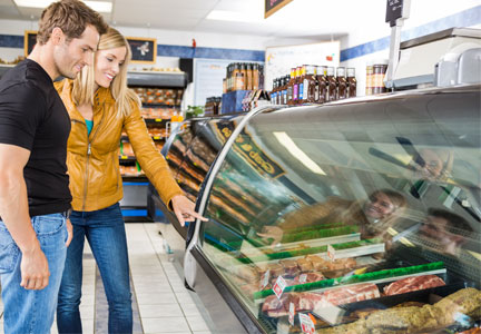 Couple choosing meat in deli section of grocery store