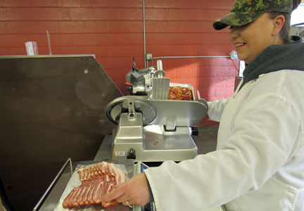 Employee slices bacon at Clark's Meat House