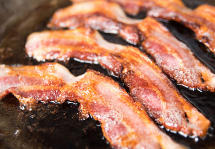 bacon cooking in a seasoned pan