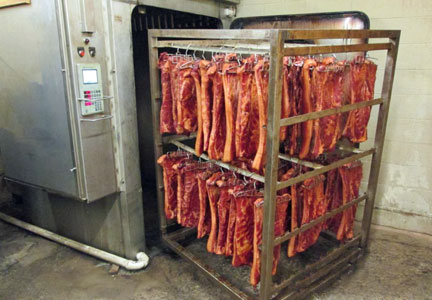 Bacon hangs from racks during smoking at Cunningham Meats