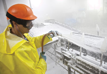 A worker applies foaming cleaner to processing equipment.