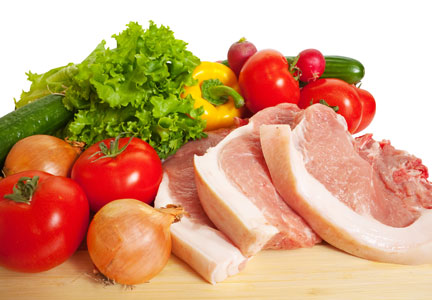 raw pork chops and fresh vegetables
