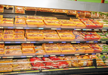 Refrigerated case containing packages of raw chicken products
