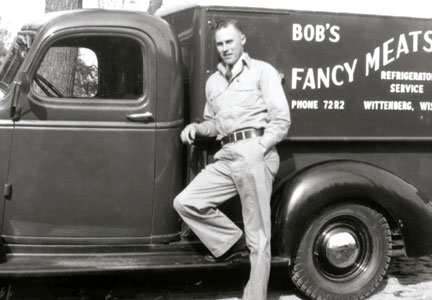R.C. Nueske, founder of Nueske's Applewood Smoked Meats, poses by a delivery truck.