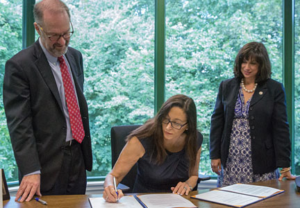 Subway CEO Suzanne Greco signs an agreement ensuring wage and hour compliance among Subway franchisees.