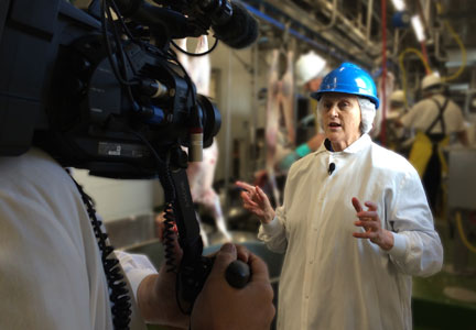 Dr. Temple Grandin participates in a tour of a lamb processing plant.
