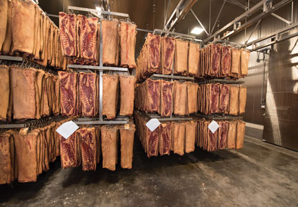 Bacon hangs on racks at Daily's new bacon processing plant in St. Joseph, Missouri.